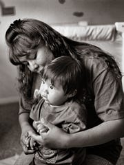 A mother and child cuddle at  Little Feet Day Care in Farmington in 1999.