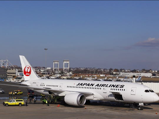 A Japan Airlines Boeing 787 Dreamliner is surrounded