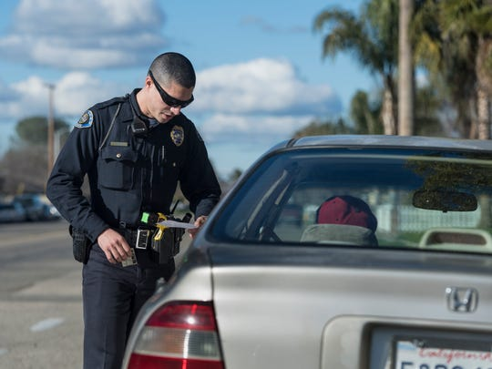 Tulare police officer Carl Santos talks with a motorist he stopped for vehicle code violations on the westside of the city Tuesday, January 24, 2017. He has been with the department for about 6 months and an officer for about three years.