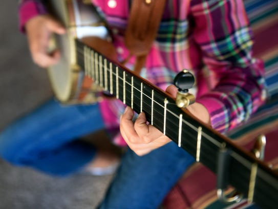 Uma Peters, 9, plays her banjo at her home Tuesday,
