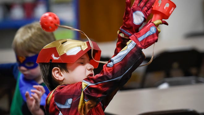 Charlie Wheeler, 5, plays the Superhero Ball and Cup Challenge during Superhero Day Friday, April 27, at All Saints Academy in St. Joseph. Money raised by the students will go to the Epilepsy Foundation.