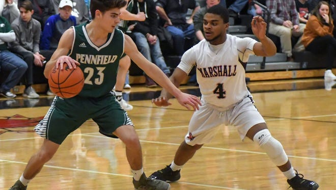 Pennfield's Ryne Petersen (23) drives the court while Marshall's Drelen Haynes (4) works on defense.