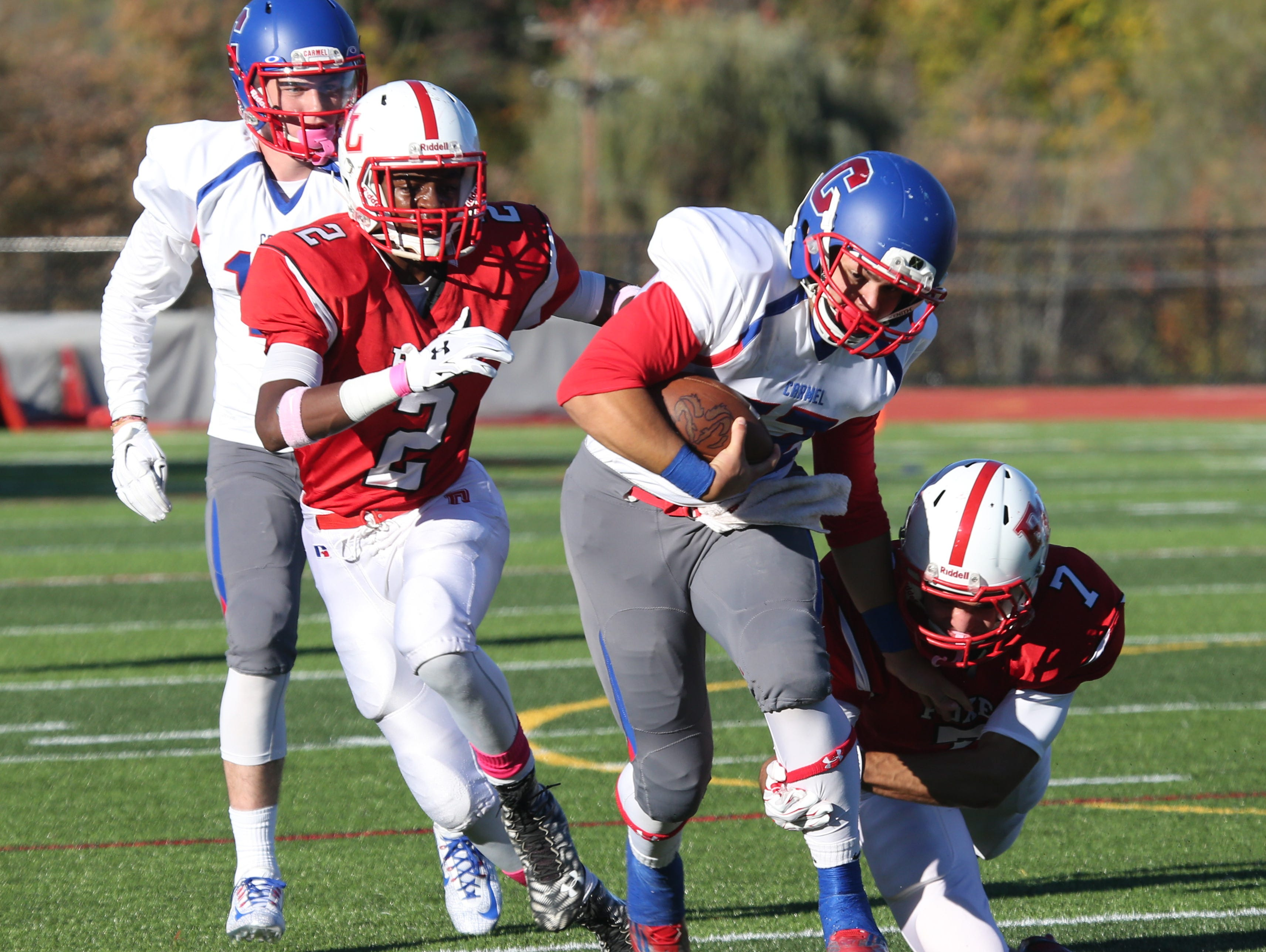 Carmel quarterback Joe Rodriguez gains some yards, as Fox Lane's Kevin Downes and Austin Brand defend during their game in Bedford, Oct. 10, 2105.