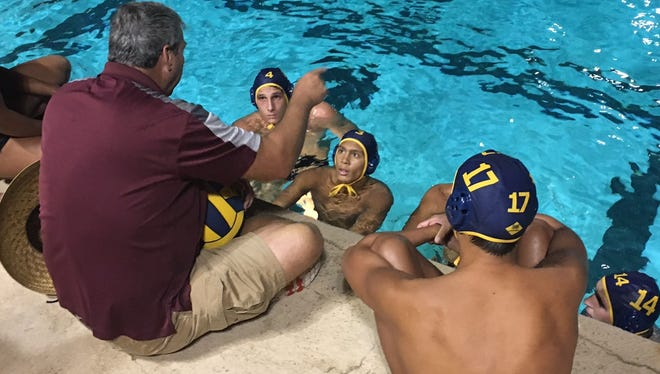 Head coach Cal Lowell instructs his La Quinta players during a timeout Thursday night. La Quinta beat Walnut 8-4 in a Division 4 playoff game. (Nov. 10, 2016)