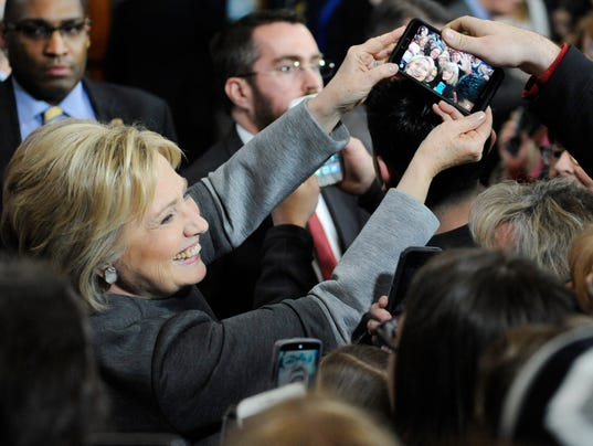 Hillary clinton holds a phone for a photo during a campaign event on