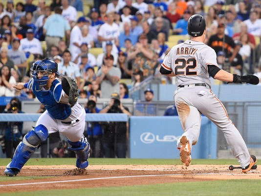 San Francisco Giants' Christian Arroyo, right, scores as Los Angeles Dodgers catcher Austin Barnes reaches for an errant throw during the second inning of a baseball game, Tuesday, May 2, 2017, in Los Angeles. (AP Photo/Mark J. Terrill)