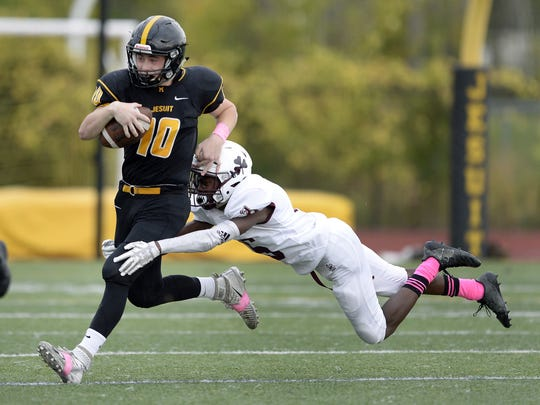 McQuaid's Hunter Walsh, left, is pursued by Aquinas' Damon Montgomery during a regular season game at McQuaid Jesuit High School on Saturday, Oct. 7, 2017.  Walsh was an All-Greater Rochester selection last season.