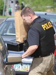 A Cincinnati Police officer loads into a car  a box with a police evidence bag on top of it.  He said it contained what appeared to be heroin,  prescription pills and cash.