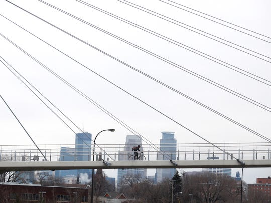 Year-round Minneapolis bike commuter Timothy Hellman, 36, originally from Bancroft, Iowa, crosses the Martin Olav Sabo Bridge over Highway 55/Hiawatha Avenue south of downtown Minneapolis. The bridge is part of the 5.5-mile Midtown Greenway.