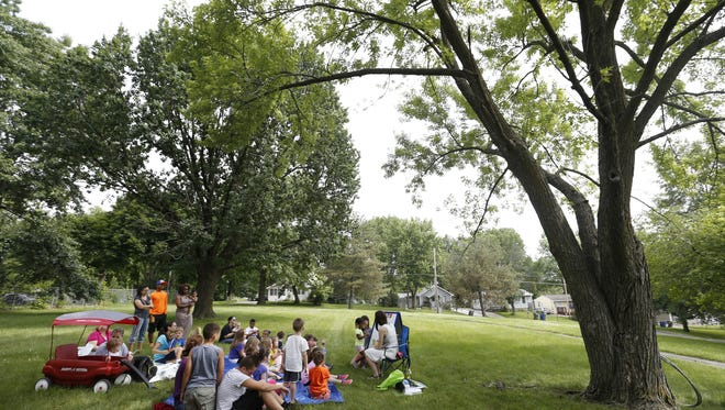 Librarian Michelle Abrahamson (center) leads a group of children through an alphabet game Thursday, June 18, 2015, during an outdoor Sunshine Storytime at the South Side Library in Des Moines.