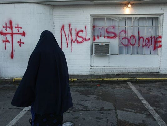 An Islamic woman goes to the Al-Farooq Islamic Center on Fourth Avenue South to pray. Vandals had inscribed Muslims Go