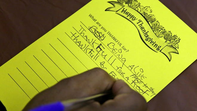 """A """"neighbor"""" writes down for what he is thankful, as he waits for Thanksgiving breakfast at Horizon House, Thursday, November 24, 2016."""