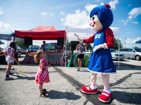Jocelyn Wright, 5, of West York, looks up at a waving Salie Utz on July 24 during the Utz Summer Bash at the Utz Quality Foods outlet store on Carlisle Street in Hanover.