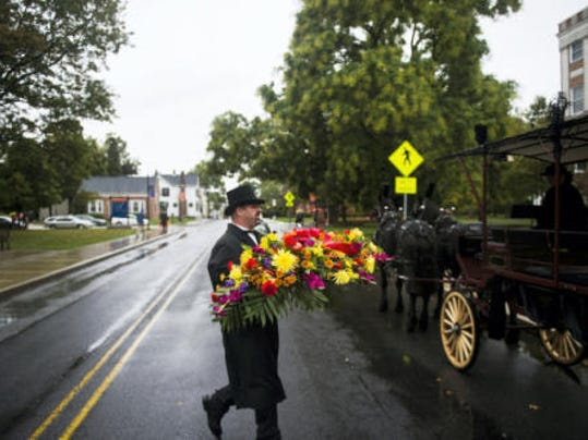 Doug Stephens, with the Victorian Carriage Company, carries a spread of funeral flowers to be ushered to Evergreen Cemetery in a horse drawn carriage Friday for the funeral procession of James Getty, a well-known President Abraham Lincoln re-enactor.