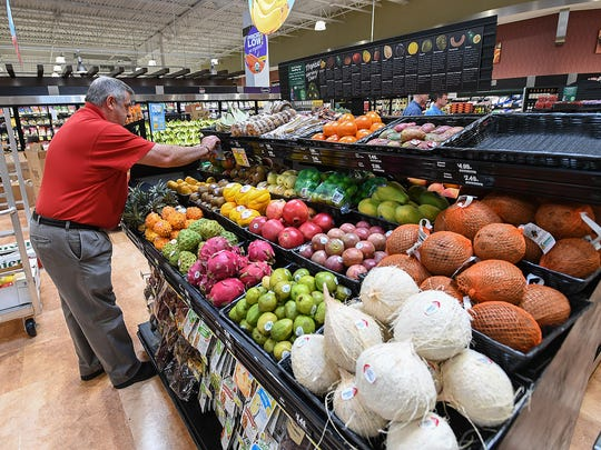 Brett Blackman arranges the tropical fruit section at the new Harris Teeter grocery store on Augusta Street in Greenville Tuesday, July 10, 2018. The store is scheduled to open Wednesday.