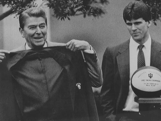 Washington -- President Ronald Reagan holds up a red
