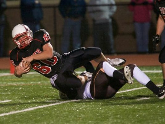 Dover's Cameron Beckman recovered a fumble and is tackled by a Milton Hershey defender during Friday's District 3 Class AAA first-round game. Dover won, 34-6. (Mike Zortman -- GameTimePA.com)