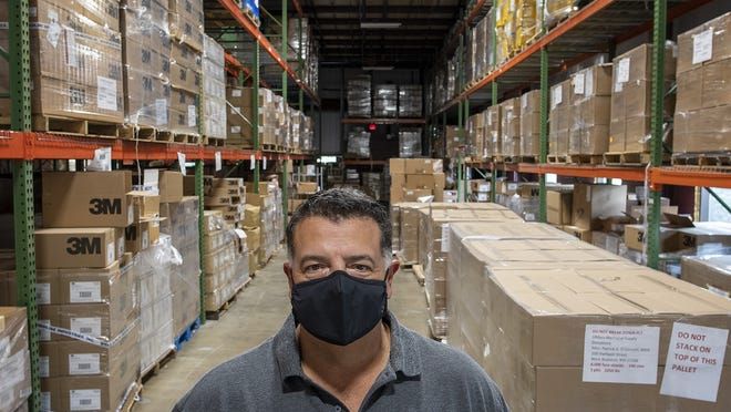 Henry Lopez is director of supply chain logistics for UMass Memorial Medical Center. He is standing inside a warehouse in West Boylston filled with personal protective equipment Friday.