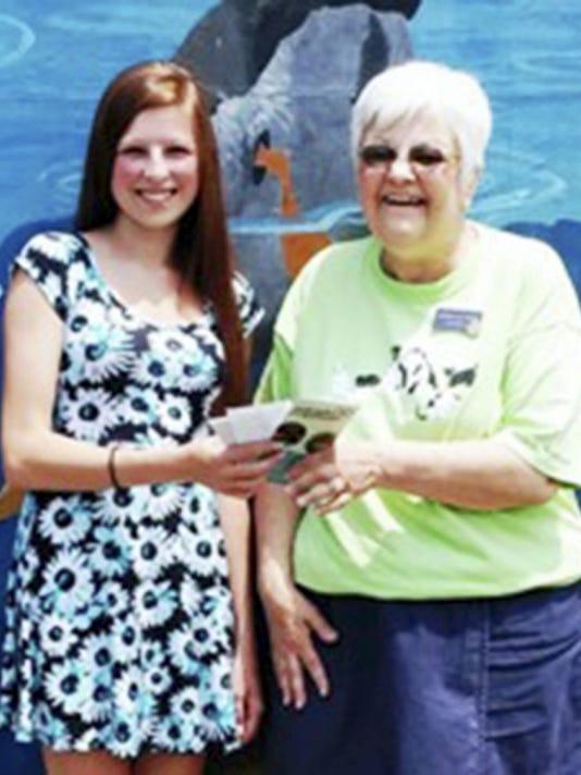 Farrah Horst, left, receives her 1,000 scholarship from Friends of All Animals President Gloria Pushnik.