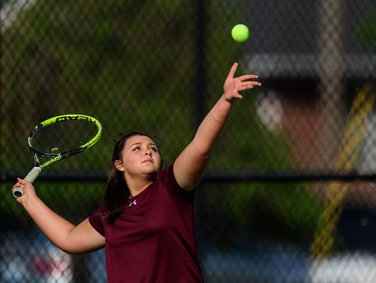 Henderson County's Kally Priest (pictured) serves up