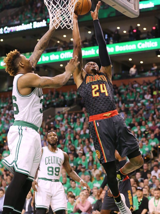 Atlanta Hawks' Kent Bazemore scores against Boston Celtics' Marcus Smart during the first half of Game 3 of an NBA basketball first-round playoff series Friday, April 22, 2016, in Boston. (Curtis Compton/Atlanta Journal Constitution via AP)
