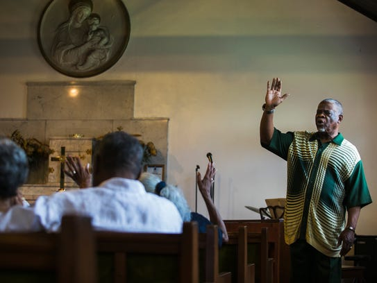 Pastor Bob Duckens prays with his congregation during