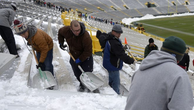 Volunteers shovel snow at Lambeau Field on Monday, Dec. 18, 2017, in preparation for the Green Bay Packers-Minnesota Vikings game on Saturday.