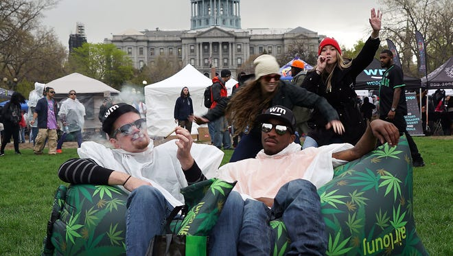 In this file photo from 2017, Kevin Barron and La-Sean Moore, both marijuana tourists from North Carolina, share a joint at Denver's Civic Center Park during the annual 420 rally while sitting on an inflatable cannabis-decorated couch.
