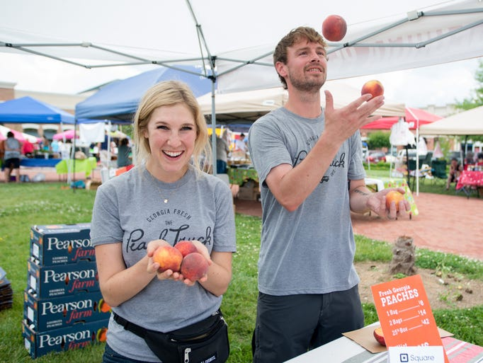 Chelsea Steele and Cary Graham with The Peach Truck have fun during the Hendersonville Farmers Market at The Streets of Indian Lake on Saturday, May 31.
