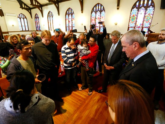 New Jersey Governor Phil Murphy, r,  bows his head