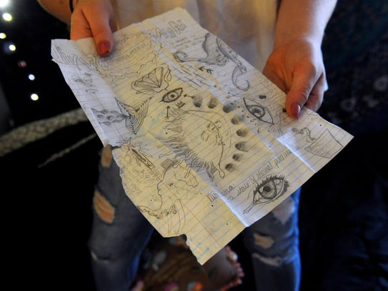 Marley Mercer holds a sheet of doodles and drawings