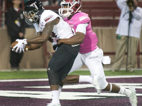 New Mexico State defensive back DeMarcus Owens tries to break up a touchdown pass to Troy's Bryan Holmes on Saturday night at Aggie Memorial Stadium.
