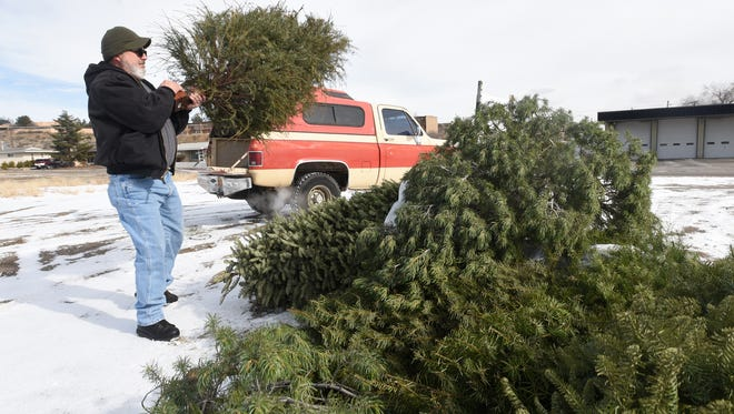 Paul Vigil tosses his Christmas tree on to the recycling pile Saturday next to Farmington Fire Department Station No. 5 at 20th Street and Butler Avenue.