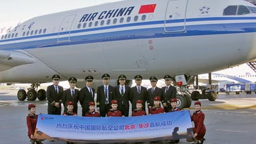 Air China crew members celebrate the airline's inaugural flight to Warsaw, Poland, on Sept. 21, 2016.