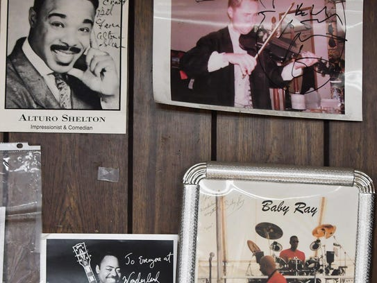 Many autographed photos of artists and musicians hang