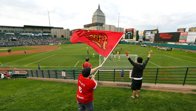 WNY Flash fan Sabrina Beach of Webster waves the team's flag as they score for a 1-1 against the Seattle Reign in the first half at Frontier Field. Sabrina has been to every game played by the Flash.