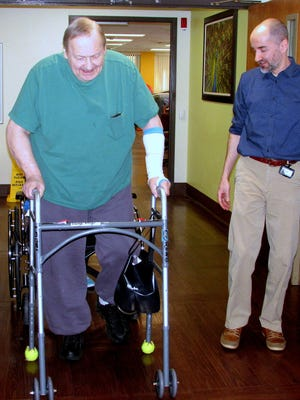 Under the watchful eye of physical therapy assistant Andy Miller, George Klugo walks down the hallway at the Corning Center for Rehabilitation and Healthcare.
