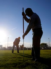 At right, Volunteer Dave Pixton on Friday drives a stake into a field as volunteers help set up for the Rotary Club and Blue Star Mothers' Healing Fields at the Farmington Boys and Girls Club.