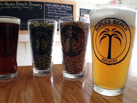 Naples Beach Brewery's Imperial Pub Ale, left, and Weizen, right, two of the brewery's products, flank pint glasses filled with hops and malted barley.