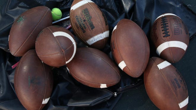 Footballs lie in an empty bag before the start of a high school football game.