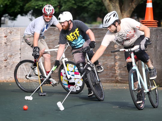 Tucker Schwinn, right, tries to get the ball away from Kyle Roland, center, as Evan Cromer, left, approaches during the Indy Bike Polo team's practice on a court in Arsenal Park at 46th and Haverford on Tuesday, July 1, 2014.