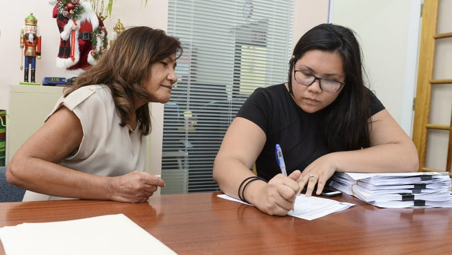 Amanda Blas, right, the governor's deputy press secretary, picks up documents requested through the Freedom of Information Act at the Guam Legislature from its Chief Financial Officer Agnes Cruz on Jan. 5.