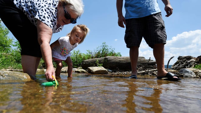 "Evelyn Blevins, 2, of Columbia, plays with her grandmother Deb Greenya, left, and dad Adam Greenya, right, in a stream just off the Susquehanna River in Lower Windsor Township. Parts of the Susquehanna River are considered ""impaired"" due to agricultural pollution and invasive species."