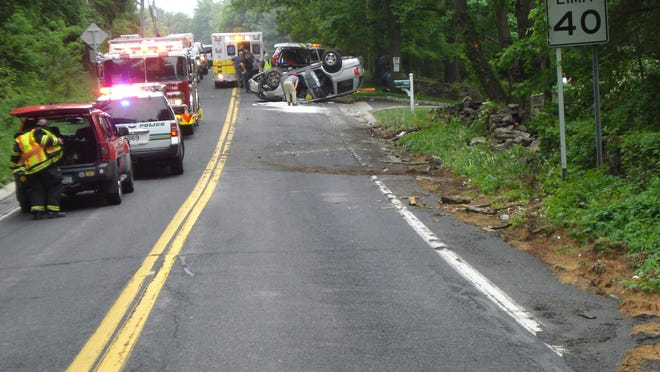 Responders at the scene where a minivan hit a stone wall, went airborne and crashed onto a Ford Mustang on Long Ridge Road, May 28, 2015. The minivan's driver was seriously injured.