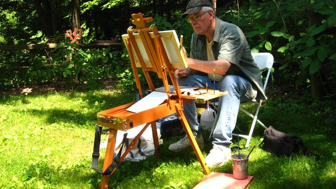 Plein air artist Bruce Bundock works on a painting in the outdoors.