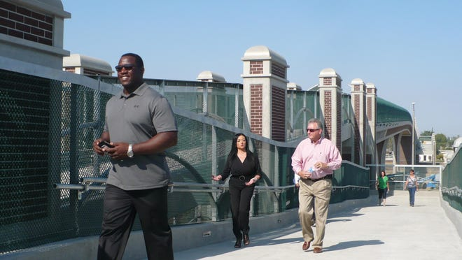 Tulare Vice Mayor Carlton Jones, front, and council members Maritsa Castellanoz and Craig Vejvoda walk on the pedestrian bridge on Friday. The bridge seeks to bring safety to the area.