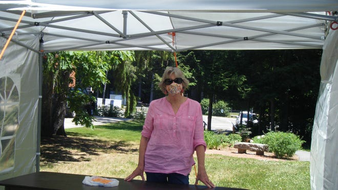 """Susie Gilbert, director of the Kensington Public Library, stands in the tent used for """"curbside service,"""" part of her gradual plan for reopening."""