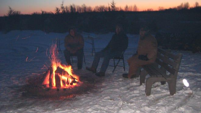 Visitors enjoy refreshments near the bonfire.