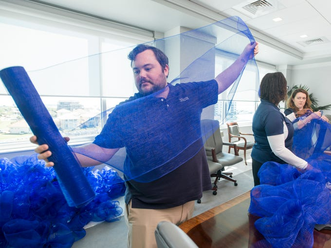 Kyle Ottley and fellow employees make big blue bows