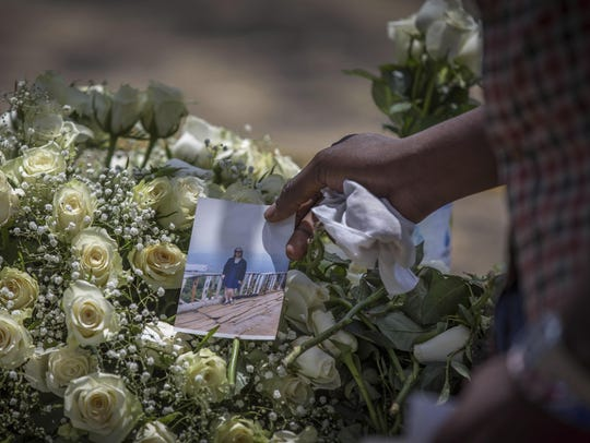 A family member puts a photo on flowers at the scene
